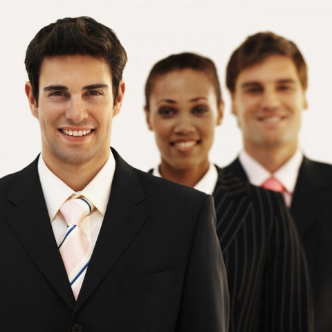 Front view portrait of three business executives smiling